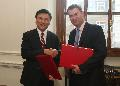 Professor Chan (left) and Mr Gauke exchange documents after signing the comprehensive agreement for the avoidance of double taxation.